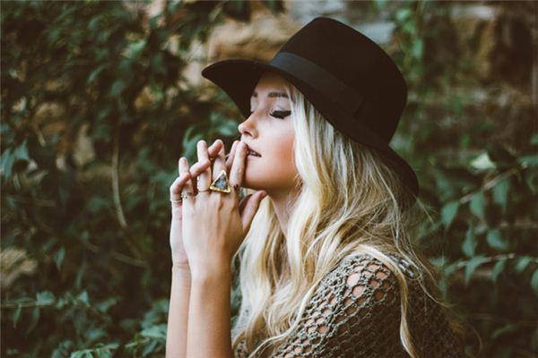 What is the meaning and symbol of wearing a black hat in a dream?